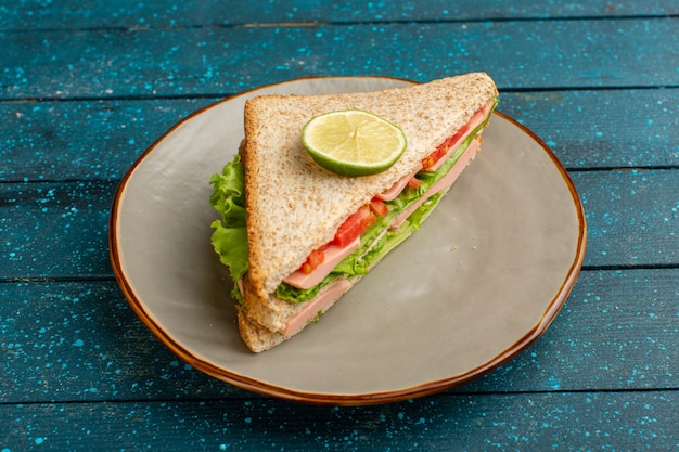 ブルーのプレートの中にグリーンサラダトマトとハムのおいしいサンドイッチ