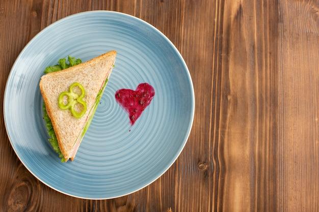 Вкусный бутерброд с зеленым салатом, помидорами и ветчиной внутри тарелки на коричневом