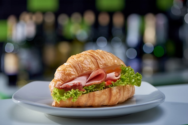 Delicious sandwich with greens, ham and  vegetables in cafe.