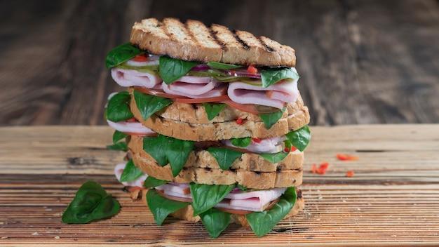 まな板の上にハムとハーブのクローズアップとおいしいサンドイッチ Premium写真