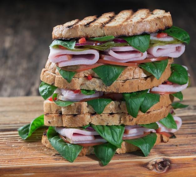 まな板の上にハムとハーブのクローズアップとおいしいサンドイッチ
