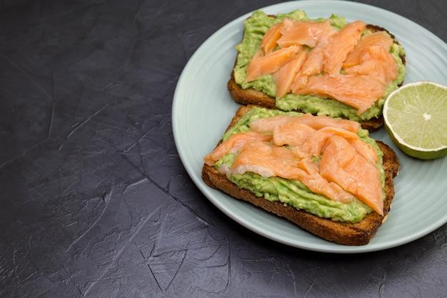 Вкусный бутерброд с ржаным хлебом, авокадо и лососем на белой тарелке на черном фоне