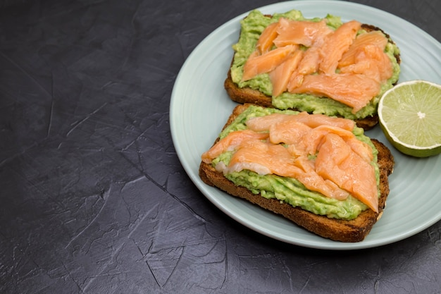 Delicious sandwich with rye bread avocado and salmon on a white plate on black background