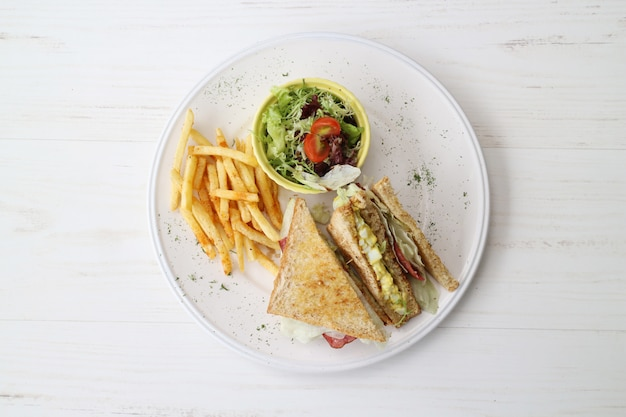 Delicious sandwich with salad and french fries on the white plate and white table