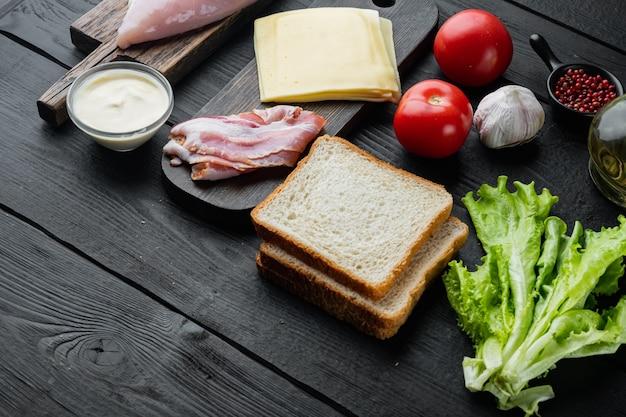 텍스트 복사 공간이 있는 검은색 나무 배경에 구운 빵 재료를 넣은 맛있는 샌드위치