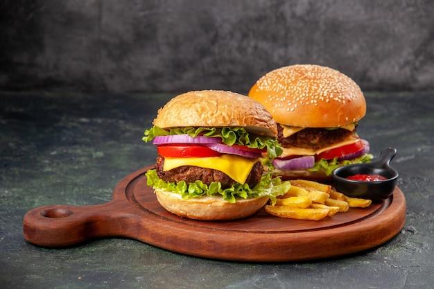 おいしいサンドイッチは、空きスペースのある暗いミックス色の表面に木のまな板の上にケチャップをフライド ポテトします。