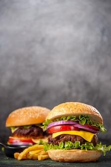 垂直ビューで暗いミックス色の表面に木製のまな板においしいサンドイッチ フライド ポテト