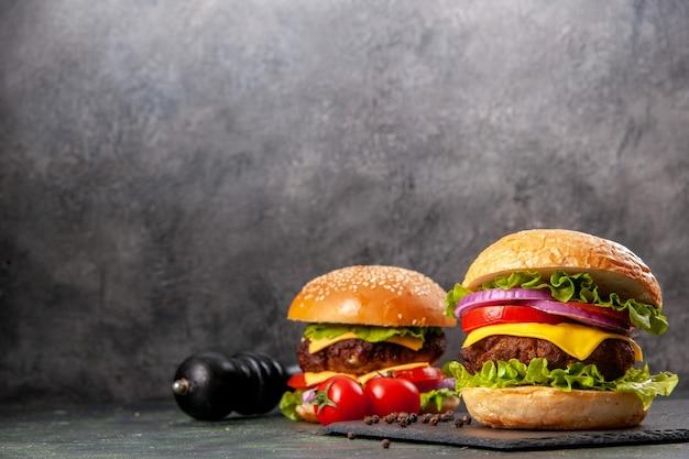 Вкусные бутерброды с перцем и помидорами на черной доске слева на поверхности темного цвета