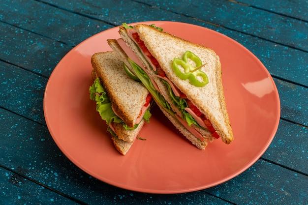 青の桃のプレートの中にグリーンサラダハムとトマトが入ったおいしいサンドイッチ