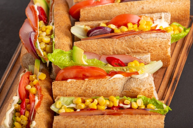 Delicious sandwiches with ham vegetables and sauce close up on a dark table