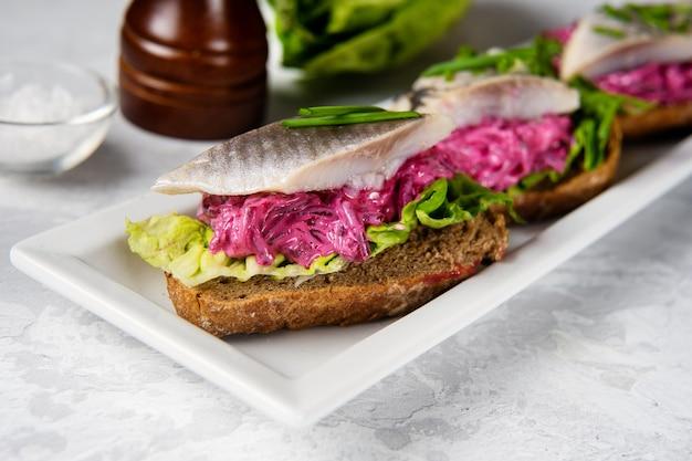 청어, 비트 뿌리 및 그린 샐러드 잎으로 맛있는 샌드위치