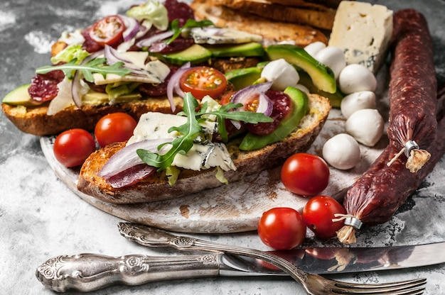 Delicious sandwiches with smoked sausage, avocado, cheese, cherry tomatoes, red onions and arugula.