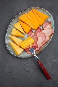 어두운 배경에 파란색 접시에 맛있는 소시지와 치즈 슬라이스