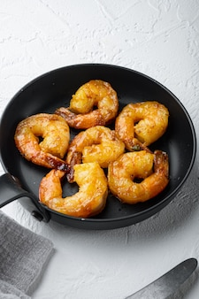 Delicious sauteed shrimp with cajun seasoning, curry and lime set, on frying iron pan, on white