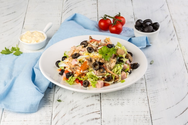 Delicious savory summer or autumn salad with olives, ham, pepper, and lettuce