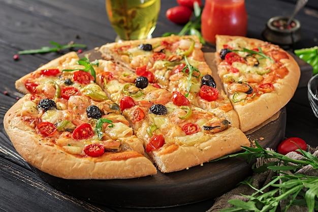 Delicious seafood shrimps and mussels pizza on a black wooden table.