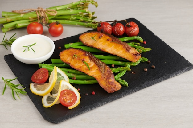 소박한 접시에 맛있는 계절 그린 아스파라거스와 슬라이스 훈제 연어