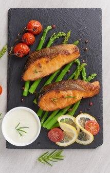 Вкусная сезонная зеленая спаржа и нарезанный копченый лосось на деревенской тарелке