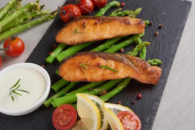 Deliziosi asparagi verdi stagionali e salmone affumicato a fette su piatto rustico