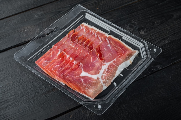 Delicious serrano ham jamon set, on black wooden background