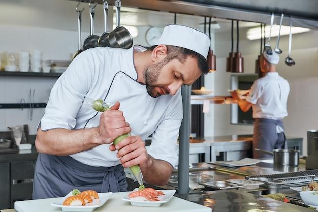 おいしい新鮮な寿司職人が、モダンな業務用厨房で提供する寿司を準備します