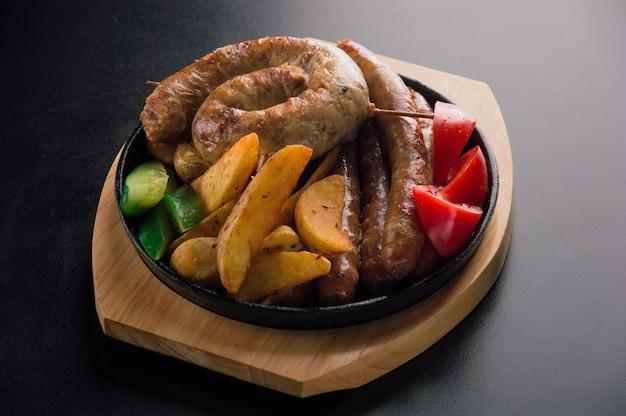 Вкусный набор баварских сосисок, тонких колбасок из говядины, жареного картофеля и свежих овощей.