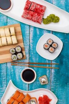 握り寿司の美味しいセットは、伝統的な醤油と箸を添えて、フラットは青い木製のテーブルの上に置きます。おいしい日本のシーフード、トップビュー