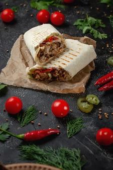 어두운 돌 테이블에 맛있는 샤와르마와 라바쉬 타코. 패스트 푸드 레스토랑. 패스트 푸드의 건강 옵션입니다. 쇠고기 고기와 야채를 곁들인 맛있는 신선한 랩 샌드위치, 전통 중동 스낵