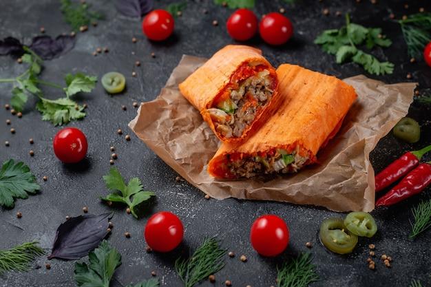 어두운 돌 탁자에 있는 치즈 라바시에 있는 맛있는 샤와르마와 타코. 패스트 푸드 레스토랑. 패스트 푸드의 건강 옵션입니다. 쇠고기 고기와 야채를 곁들인 맛있는 신선한 랩 샌드위치, 전통 미들