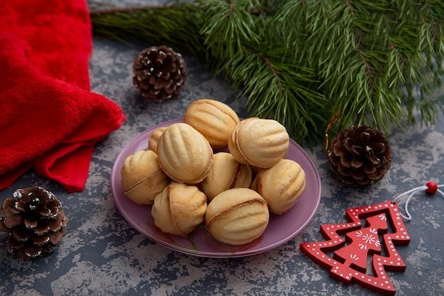 달콤한 농축 우유와 크리스마스 트리와 조명의 배경에 짓 눌린 된 견과류의 충전 물 가진 호두 모양의 맛있는 치즈, 아몬드 쿠키. 크리스마스 치료.