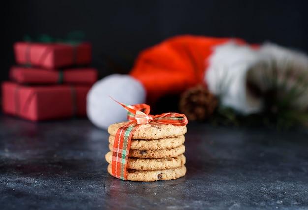 초콜릿 조각, 빨간 리본, 가문비 나무 장식, 산타 모자, 쇼티와 함께 맛있는 쇼트 브레드 쿠키. 크리스마스 구성