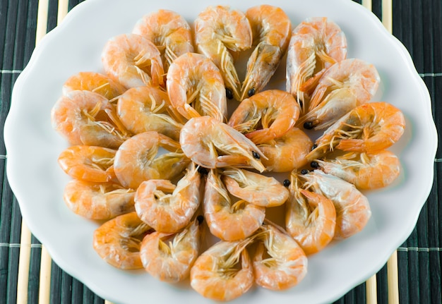 Delicious shrimp are on the plate on blue background napkin