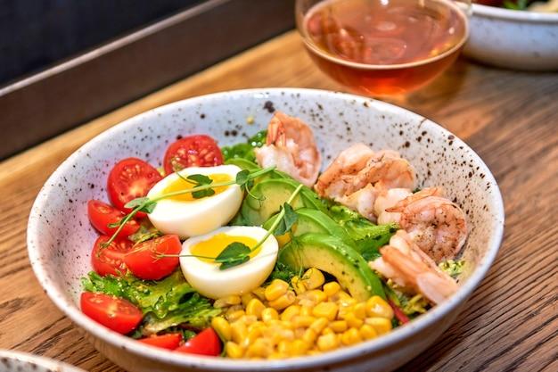 木製のテーブルの上のレストランでおいしいエビ。カフェやパブのメニューにビールと一緒に美味しいシーフード。