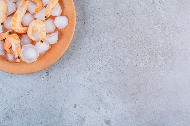 Deliziosi gamberetti in cubetti di ghiaccio in un piatto arancione su una superficie di pietra