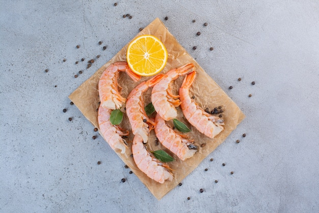 Delicious shrimps with sliced lemon and peppercorns on greaseproof paper .