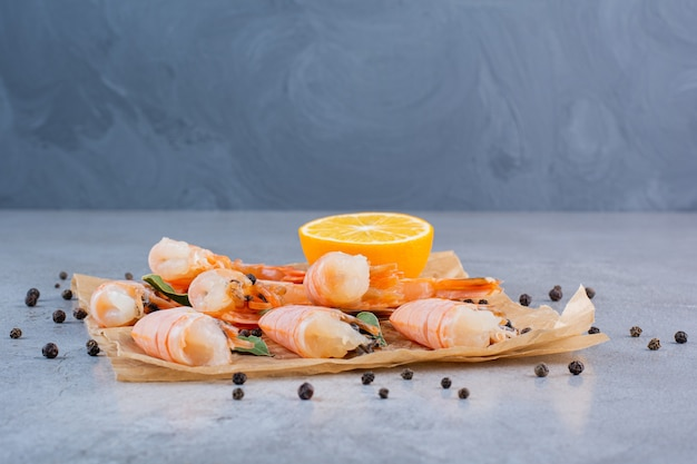 Delicious shrimps with sliced lemon and peppercorns on greaseproof paper