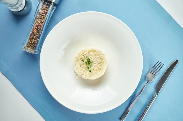 메인 코스에 대한 맛있는 반찬-파란색 식탁보에 흰색 접시에 microgreen으로 삶은 쌀. 보기 닫기