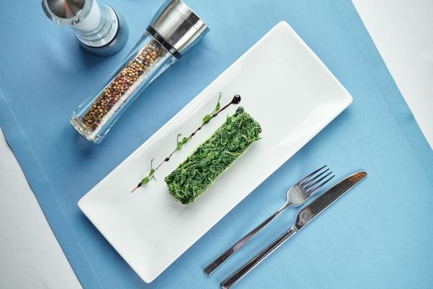 Вкусный гарнир к вторым блюдам - тушеный шпинат в сливках в белой тарелке на синей скатерти