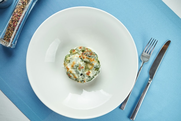 Delicious side dish for main courses - baked broccoli with melted cheese in a white plate on a blue tablecloth