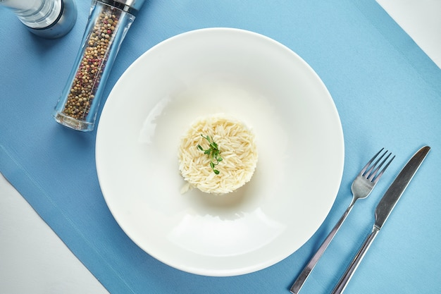Delicious side dish for main courses - boiled rice with microgreen in a white plate on a blue tablecloth. close up view