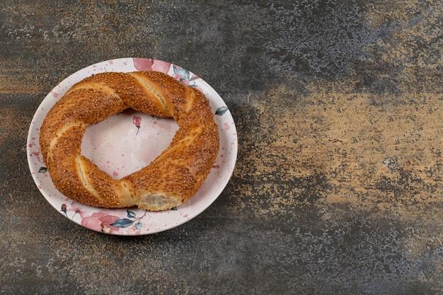 Delizioso simit con semi di sesamo su piatto colorato