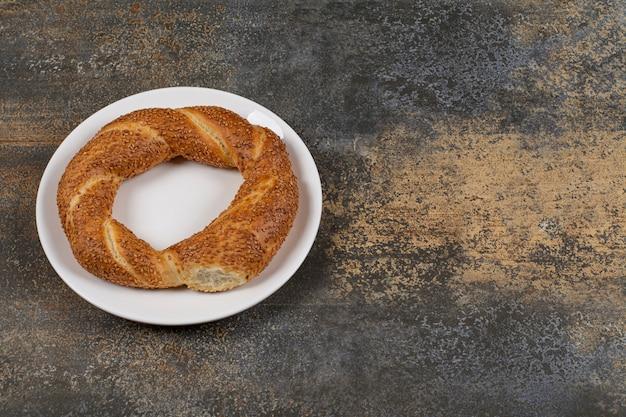 Delizioso simit con semi di sesamo su piastra bianca