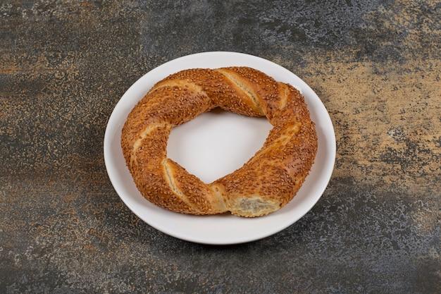 Delizioso simit con semi di sesamo su piastra bianca.