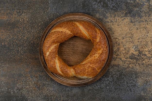 Delizioso simit con semi di sesamo su piatto di legno