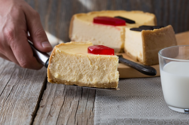Delicious slice of new york cheesecake with word  on wooden table. sweet and tasty food, coffee break concept.