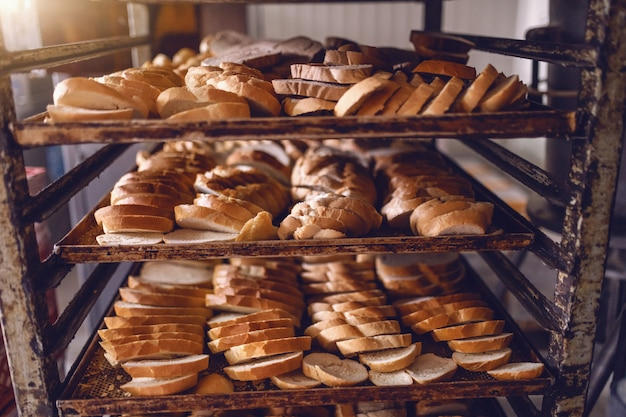 Delicious sliced baked bread align on baking trays on shelves in bakehouse.
