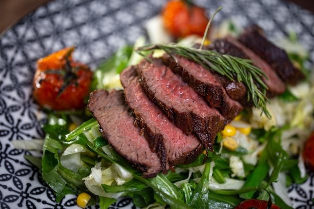야채와 허브 클로즈업으로 맛있는 슬라이스 고기. 요리사의 요리