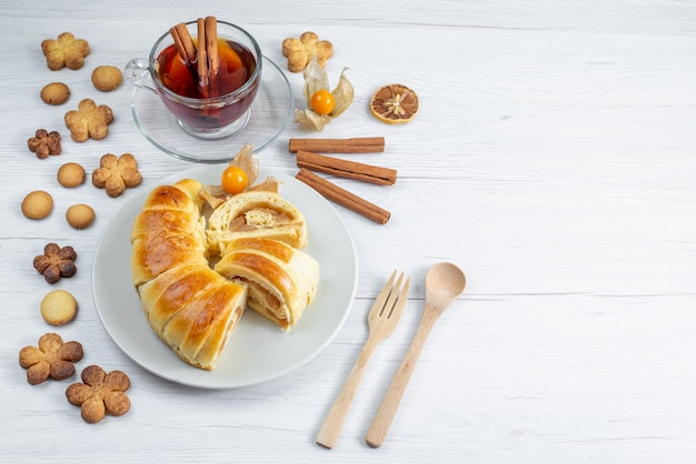 Delicious sliced pastries inside plate with filling along with tea and cookies on white , pastry cookie biscuit sweet