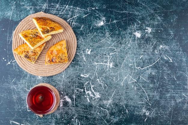Deliziosa pasticceria a fette con semi e bicchiere di succo di frutta fresco su sfondo marmo.
