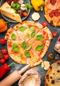 맛있는 슬라이스 피자와 피자를 만들기위한 재료. 밀가루, 치즈, 토마토, 바질, 페퍼로니, 버섯, 나무 배경 위에 롤링 핀.